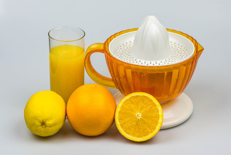 Citrus juicer with fresh squeezed juice, oranges and lemon isolated on a white background