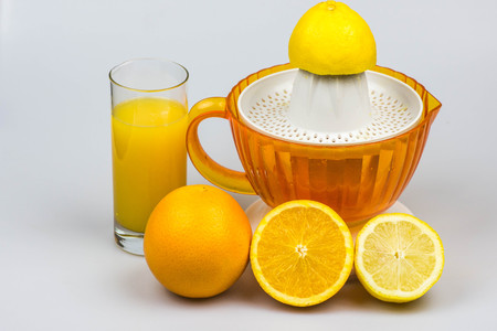 thirst quenching: Citrus juicer with fresh squeezed juice, oranges and lemon isolated on a white background