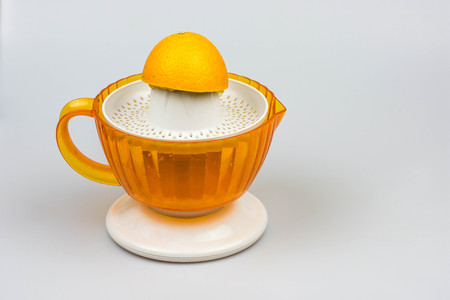 thirst quenching: Citrus juicer with orange isolated on a white background