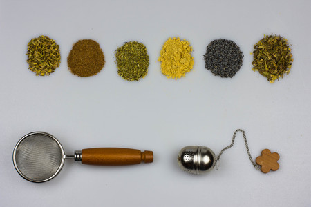 cystitis: Herbal tea ingredients with strainers - fennel seeds, cinnamon, mallow, ginger, poppy seeds, lemon balm Stock Photo