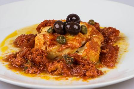 baccalà italiano con olive nere, capperi e pomodoro in un design piatto, isolato su uno sfondo bianco