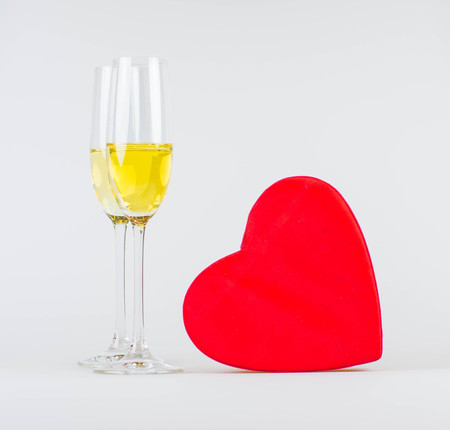 Happy valentines day greeting card with red heart and flutes of champagne