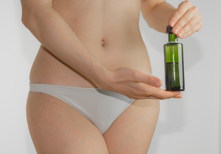 diuretic: Beautiful young woman body with a bottle of olive oil isolated on a white background