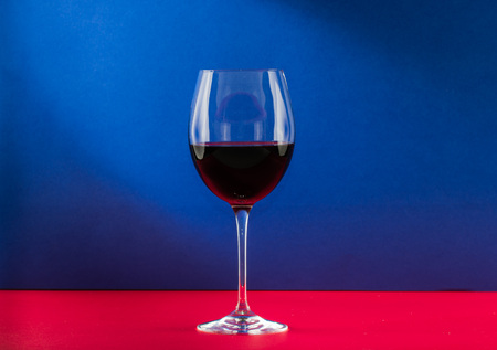 Polished still life glass of wine with nice light effect in red and blue background
