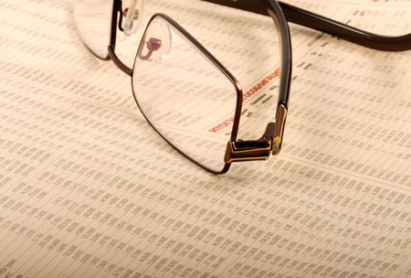 Glasses lying on a folded newspaper with business report    photo