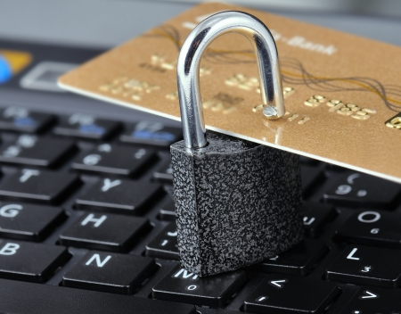 identity thieves: Tarjeta de cr�dito con el bloqueo en un port�til de fondo. Simboliza la fiabilidad y la seguridad de Internet Foto de archivo