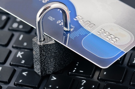 ladrones: Tarjeta de cr�dito con el candado de un port�til de fondo. Simboliza la fiabilidad y la seguridad de Internet