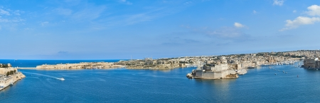 greatly: Panoramic view to Grand Harbour in Malta  Grand Harbour in Malta is a natural harbour on the island of Malta  The natural harbour has been greatly improved with extensive docks and wharves, and has been massively fortified