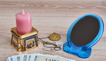 pentacle: Everything is ready for divination - pack of Tarot cards, pentacle medallion, candle in  Egyptian candlestick, mirror