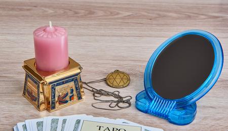 pentacle: Tutto � pronto per la divinazione - mazzo di carte dei Tarocchi, medaglione pentacolo, candela in egiziano candeliere, specchio Archivio Fotografico