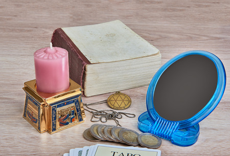 fortunetelling: Everything is ready for divination - pack of Tarot cards, pentacle medallion, candle in  Egyptian candlestick, mirror, book and coins are on the table