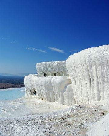 pamukkale: Winter-like landskape with white travertine instead of snow, limestone pool instead of ice and improbably blue sky in the background