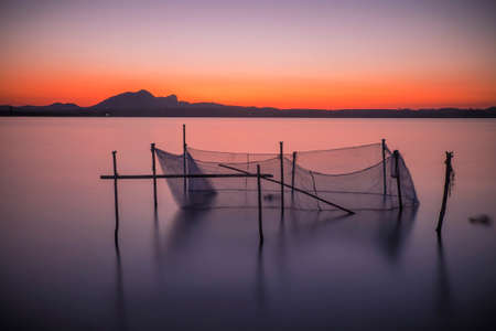 placid water: Long exposure shot of the net in the river at the twilight time.