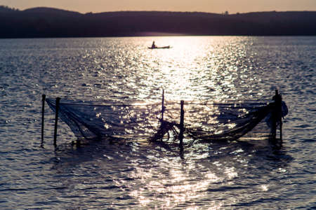 placid water: The net in the river and the boat behind. Stock Photo