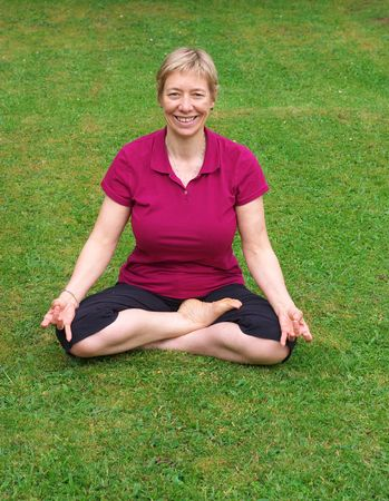 forties: blonde, caucasian woman in her forties doing yoga on the lawn, black short trousers and purple t-shirt, lotus position