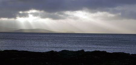 The scottish island of Arran at a stormy day, seen from the western coast of the mainland (Mull), sun rays or beams over the sea photo