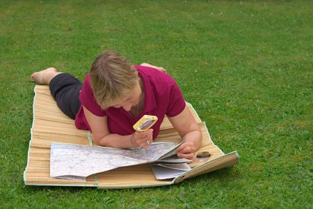 blonde, caucasian woman in her forties studying map on the lawn, black short trousers and purple t-shirt, planning next trip photo