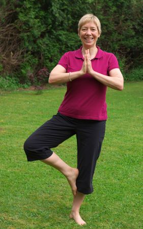center position: blonde, caucasian woman in her forties doing yoga on the lawn, black short trousers and purple t-shirt, standing on one leg