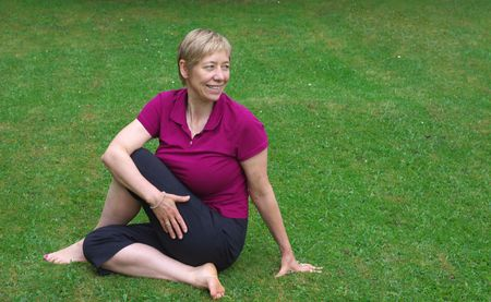blonde, caucasian woman in her forties doing yoga on the lawn, black short trousers and purple t-shirt,  photo