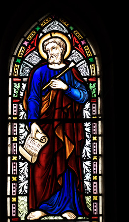 detail of victorian stained glass church window in Fringford depicting St Luke the Evangelist, a scroll in his hands with the beginning of his gospel in latin Fuit in diebus herodes