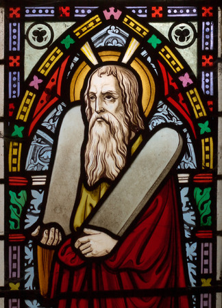 to obey: detail of victorian stained glass church window in Fringford depicting Moses with the tablets of covenant in his arms, interestingly without text, means he is pictured before climbing Mount Sinai Editorial