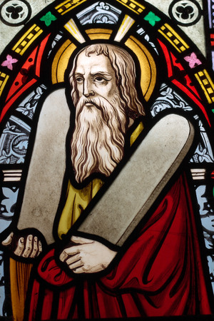 detail of victorian stained glass church window in Fringford depicting Moses with the tablets of covenant in his arms, interestingly without text, means he is pictured before climbing Mount Sinai Editorial