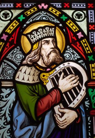 왕: detail of victorian stained glass church window in Fringford depicting King David, the author fo the psalms in the Old testament with a hand harp 에디토리얼