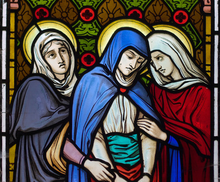 detail of victorian stained glass church window in Fringford depicting St. Mary with two other women under the cross on the first Good Friday