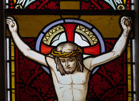 pious: detail of victorian stained glass church window in Fringford depicting Jesus nailed to the cross