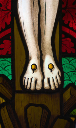 detail of victorian stained glass church window in Fringford depicting Jesus feet nailed to the cross