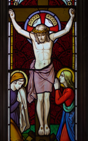 st  john: detail of victorian stained glass church window in Fringford depicting Jesus nailed to the cross with St. Mary and St. John at the feet of the cross Editorial