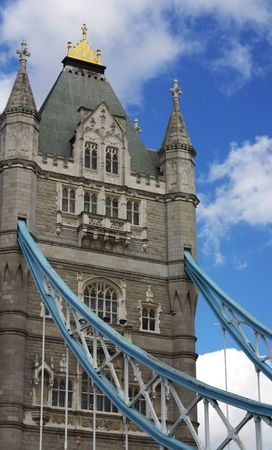 Detail of Tower Bridge (a bascule bridge) with fluffy white clouds and blue sky in Southwark, London, Uk, Europe. One of the United Kingdoms most visited tourist attractions. photo