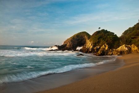 Sandy beach with rocks at sunrise photo