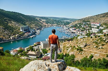 A man on top of a mountain, a view of the city from a height
