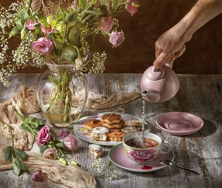 Pink flowers in a glass vase, on a clear wooden table, a hand serves classic English tea, with pastas, hot water falls into the tea cup