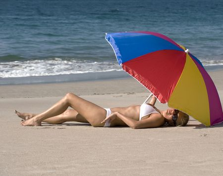 beautiful woman in white bikini lying under colorful umbrella on tropical beach Stock Photo - 6049968
