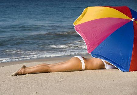beautiful woman in white bikini lying under colorful umbrella on tropical beach Stock Photo - 6049969