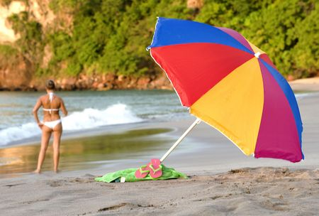 tropical beach scene with colorful umbrella, beach towel and woman in white bikin Stock Photo - 6049972
