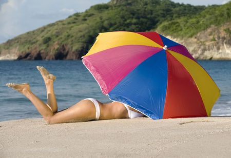 beautiful woman in white bikini lying under colorful umbrella on tropical beach Stock Photo - 6107706