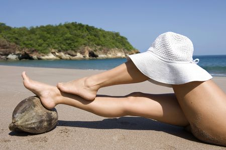 woman resting legs on coconut on tropical beach with white hat on knee, guanacaste, costa rica, central america Stock Photo - 6196427