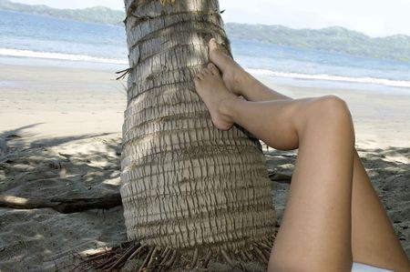 woman relaxing on tropical beach with feet resting on coconut tree Stock Photo - 6196453