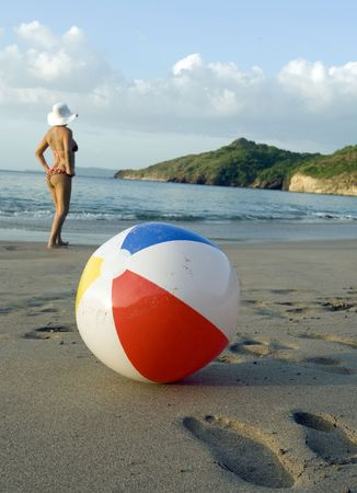 attractive woman in polka dot bikini wearing white hat standing on tropical beach in front of colorful beachball, costa rica, central america Stock Photo - 6331176