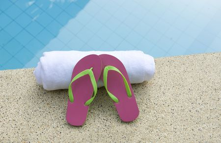 pink and green shoes/flip flops resting on white towel next to blue water of swimming pool Stock Photo - 6472660
