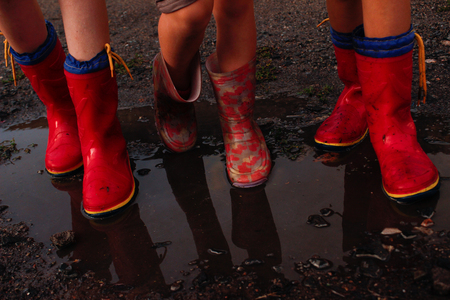kinderen na de regen met rubberen laarzen Stockfoto