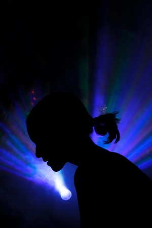 the silhouette of a person in disco background. color lasers in smoke. Side view Imagens