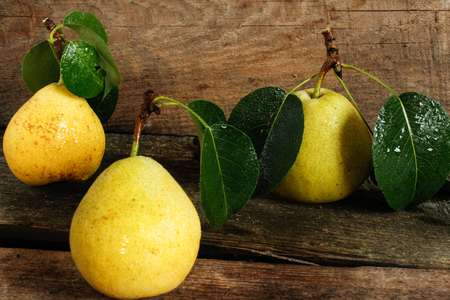 tree ripe pears on a wooden worktop. close-up. side view