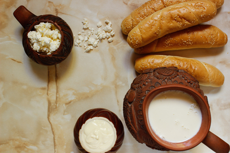 Composition of dairy products and rolls. Milk in a clay jug, cottage cheese and sour cream in clay pots, buns. View from above Stock Photo
