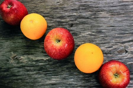 apples and tangerines on a wooden table. View from above Stock Photo