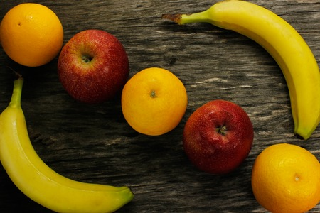 ffruit platter of resh mandarins and red apples and bananas on gray wooden table view from above Stock Photo
