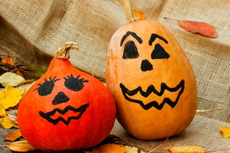 Halloween. a cheerful Halloween pumpkin among the leaves. Side view Stock Photo